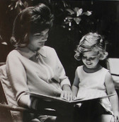 Black & white photograph of Jackie Kennedy reading with a child