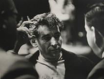 Leonard Bernstein smokes and talks with two gentlemen in New York City, 1950s