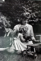 Black & white photograph of Jackie Kennedy sitting on a lawn with a child
