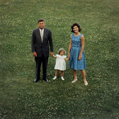 Color photograph of Jackie Kennedy wearing a blue dress and JFK with child on a lawn