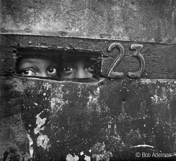 BOB ADELMAN (1930-2016) Peering through a mail slot, Brooklyn, New York City photo 1964 [printed later]  gelatin silver print, edition of 15, signed, numbered  Paper Size: 16 x 20 inches | 40.6 x 50.8 cm