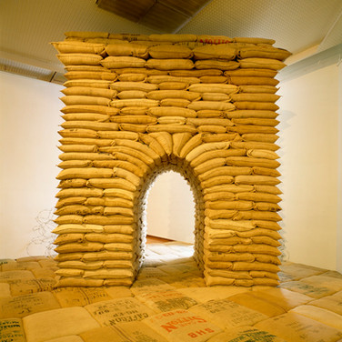 "Nobuho Nagasawa Arcus, 1993 sandbags, barbed wire, hourglass 13 x 12 x 9 feet  From ""Invisible Nature,"" Ludwig Museum, Budapest, Hungary, 1993"