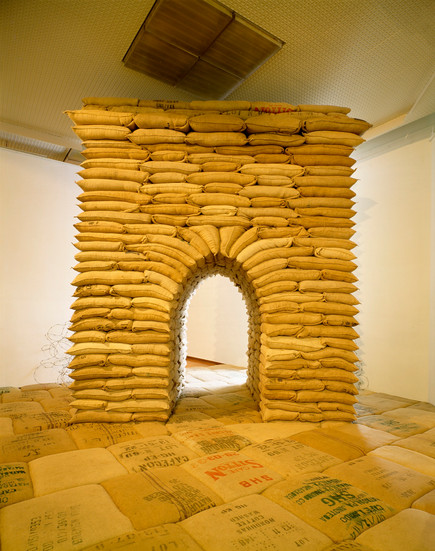 """NOBUHO NAGASAWA Arcus (1993) sandbags, barbed wire, hourglass 13 x 12 x 9 feet  Installation from """"Invisible Nature"""" at Ludwig Museum, Budapest, Hungary, 1993."""