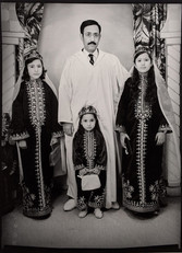 1960s black & white photograph a father with three daughters in middle-eastern garb, a photography studio
