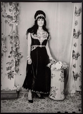 1960s black & white photograph of a woman wearing an embroidered dress in a photography studio