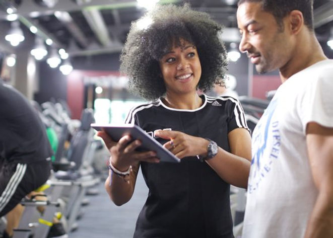 woman holding a tablet in front of man, with membership details