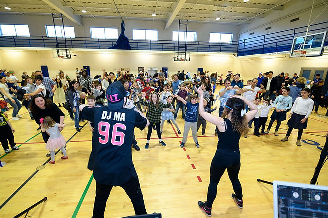 deejays teaching a dance to hundreds of children inside MNjcc gymnasium at Yom Haatzmaut party