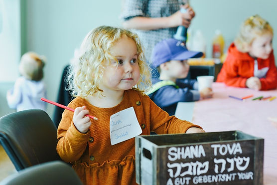 little girl writing a Rosh Hashana message