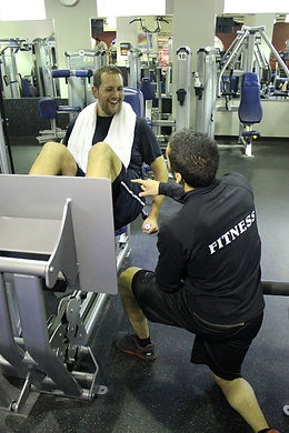 an mnjcc personal trainer working with a client on a leg press machine