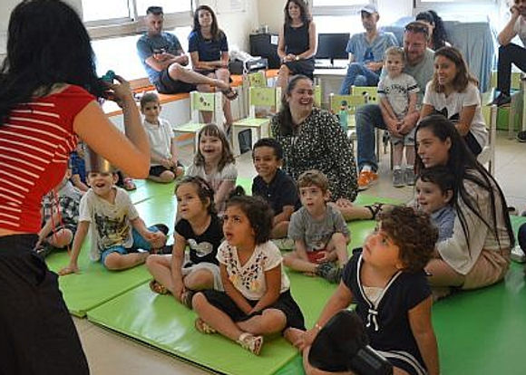 israeli children and their parent sitting on the floor being entertained by a performer