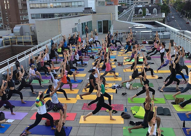 Rooftop Yoga Class with about 100 people all in the same pose