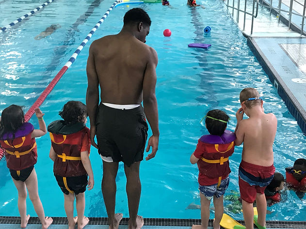 camp counsellor about to jump into pool with four campers