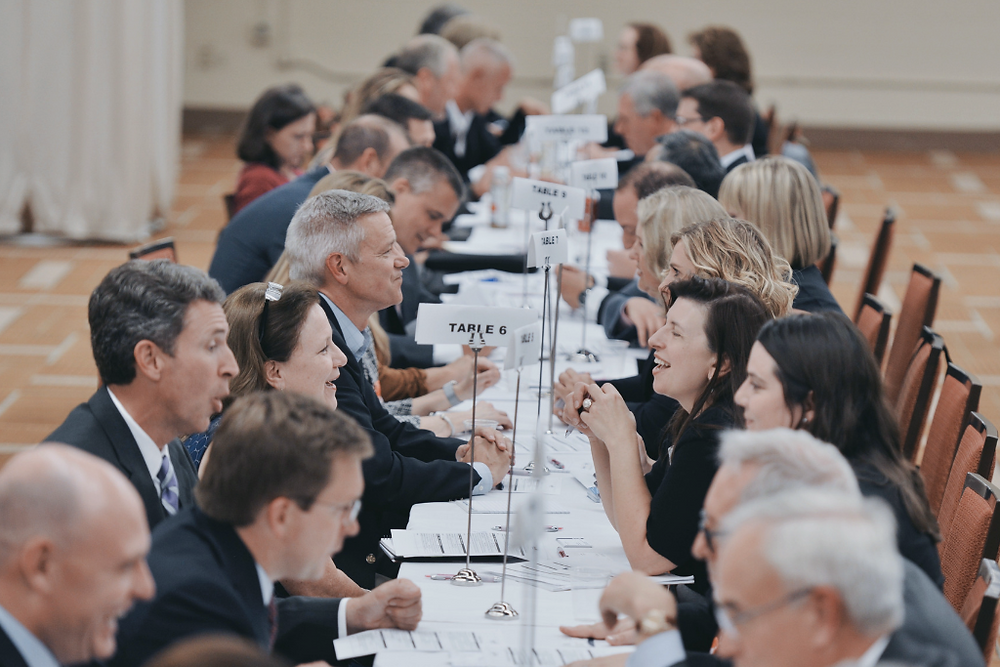 people seated along a table at a speed networking event