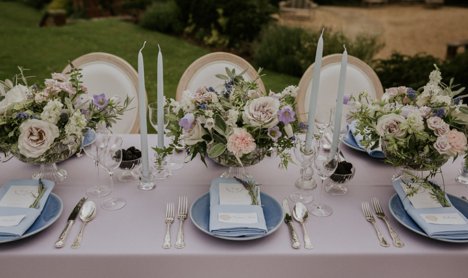 Pale blue and lilac wedding table design with blue taper candles by Emma Jane Weddings