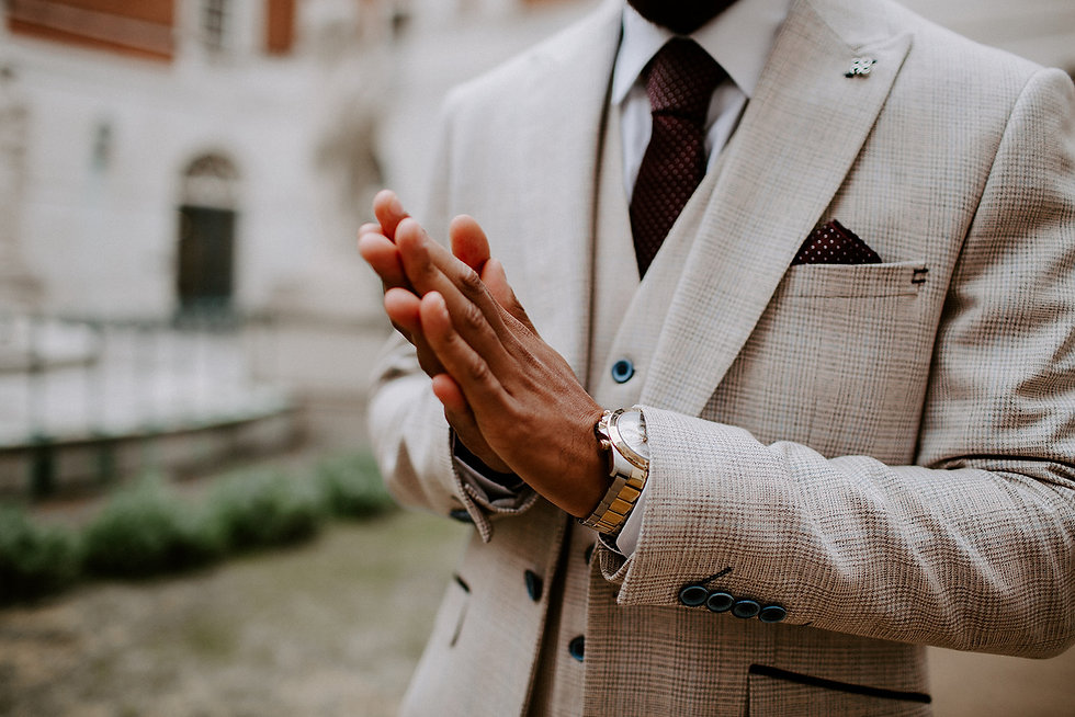 Groom wearing a suit, tie, pocket square and watch with his hands placed together