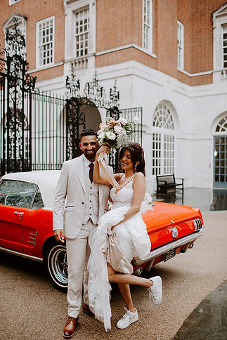 Wedding couple standing in front of red Ford Mustang at BMA House London
