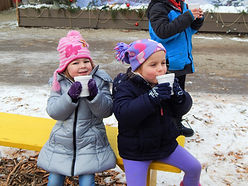 Two young kids drinking hot cocoa on a bench in winter.