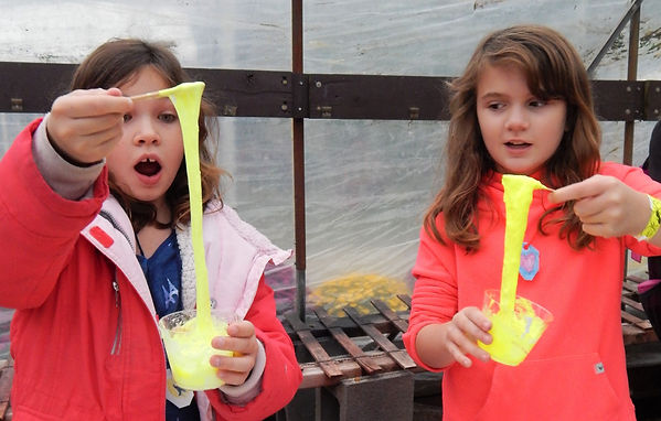 Two young girls creating slime.