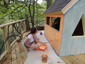Young woman volunteering and painting a minature treehouse