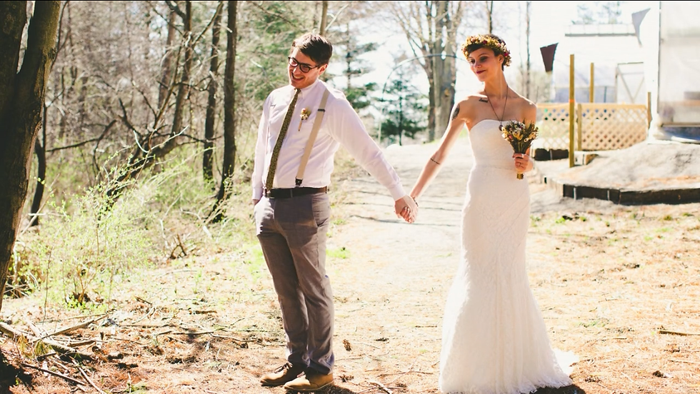 Newlyweds, a man and a women, holding hands on a trail.