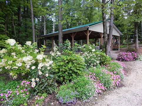 Outdoor rental pavilion surrounded by flowers and woods.
