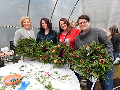 Group of women holiding up the wreaths they made.