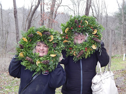 Two people holding up wreaths with pinecones, dried oranges, cinnamon and berries in it.