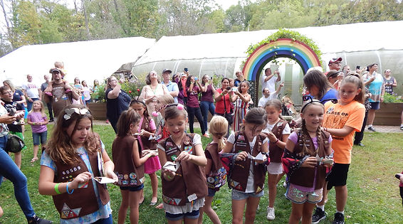Rainbow arch with a crowd of people watching butterflies be released