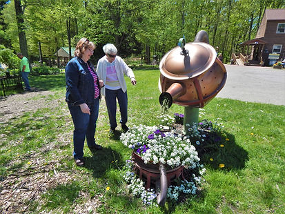 two women, one elderly, pointing at an outdoor art display with flowers at Art in Bloom