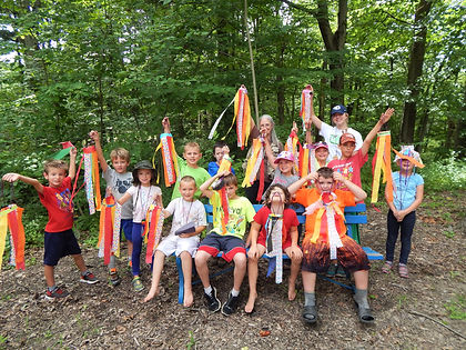 Group of kids lifting up a hanging craft they made at Nature Camp