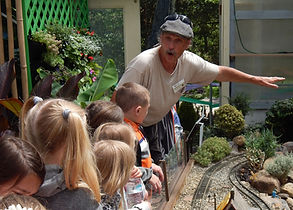 Older man instructing young children about plants