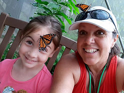 woman and child with monarch butterfies on head