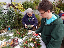 Two women creating their holiday wreaths.
