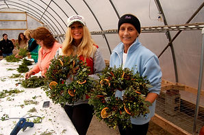 Women showcasing wreaths they made