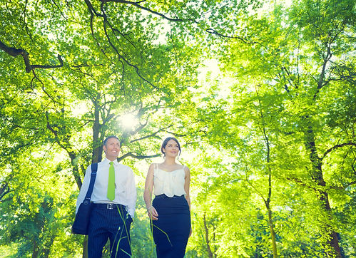 Business partners, a man and woman, walking through woods.