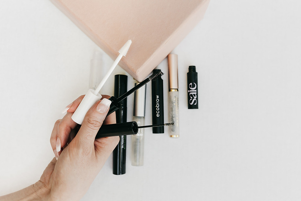 A hand holding three clear brow gel wands