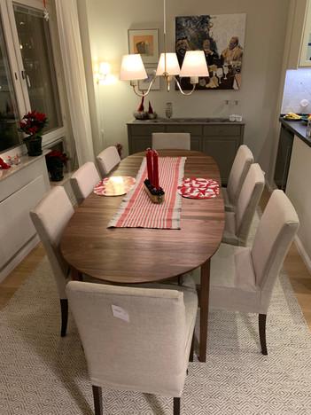 """Matplatsen är hemmets hjärta. Valnöten i det mjukt rundade bordet skapar ombonad känsla. Tillsammans med de linnestoppade stolrna och den klassiksa mjuka indirekta belysningen inbjuder det till långa sittningar. Noter gärna den infällda vinkylen i """"döda hörnet"""" på kökets bardisk."""