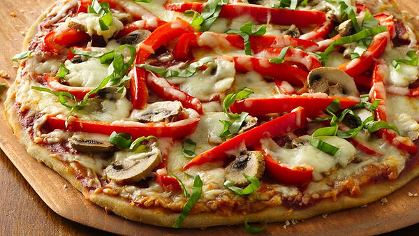 vegetable pizza on a wooden peel