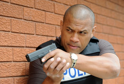Actor Aaron Fa'Aoso portraying a police officer, he is holding a gun
