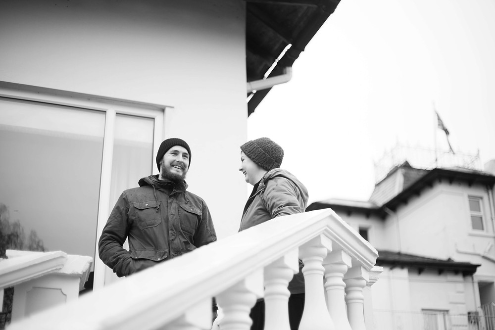 Couple laughing on an outdoor staircase at their pre wedding shoot at Thornton Hall Hotel