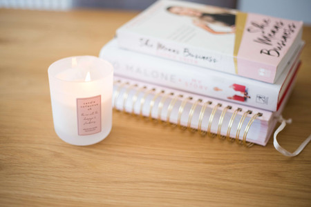 Lit candle next to books and notepads Candle collective uk
