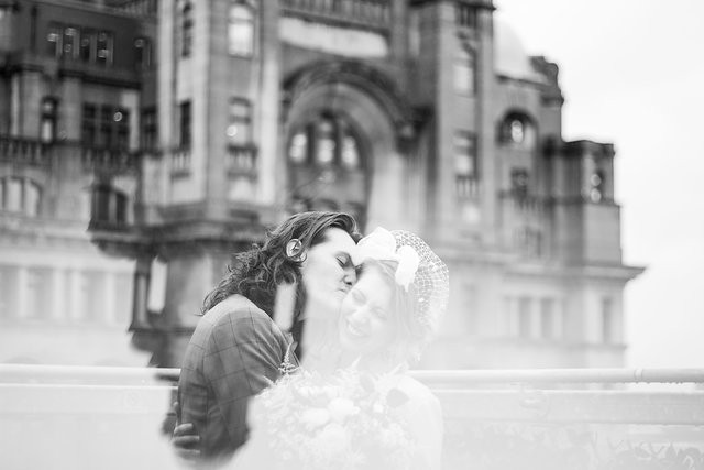 Bride and groom on roof of Oh Me Oh My with reflection of Liver Building