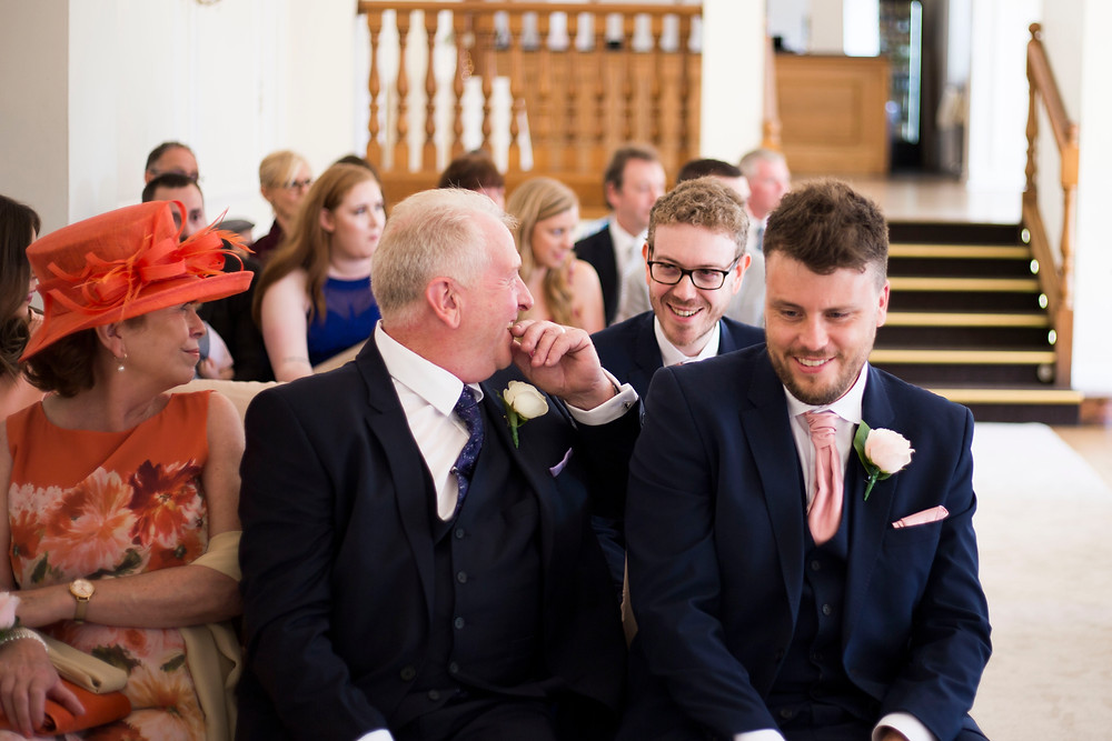 Groom, best man, and grooms parents laughing as they wait for the bride to enter the wedding ceremony