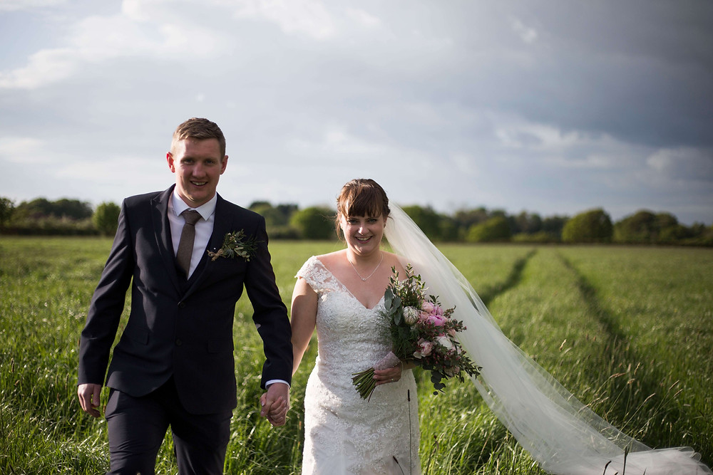 Bride and groom walking through field Parr Hall Farm Wedding