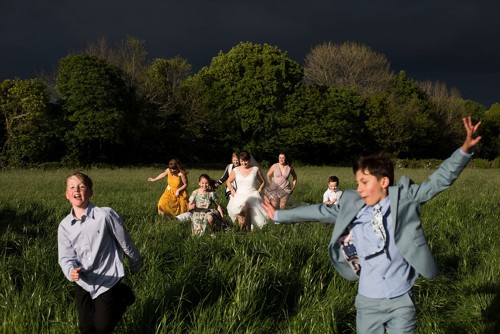 Bride and guests running through field Parr HAll Farm wedding