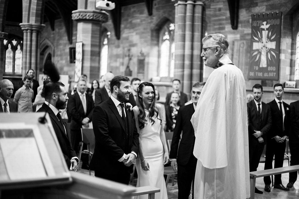Black and white image of bride and groom laughing during their church wedding ceremony