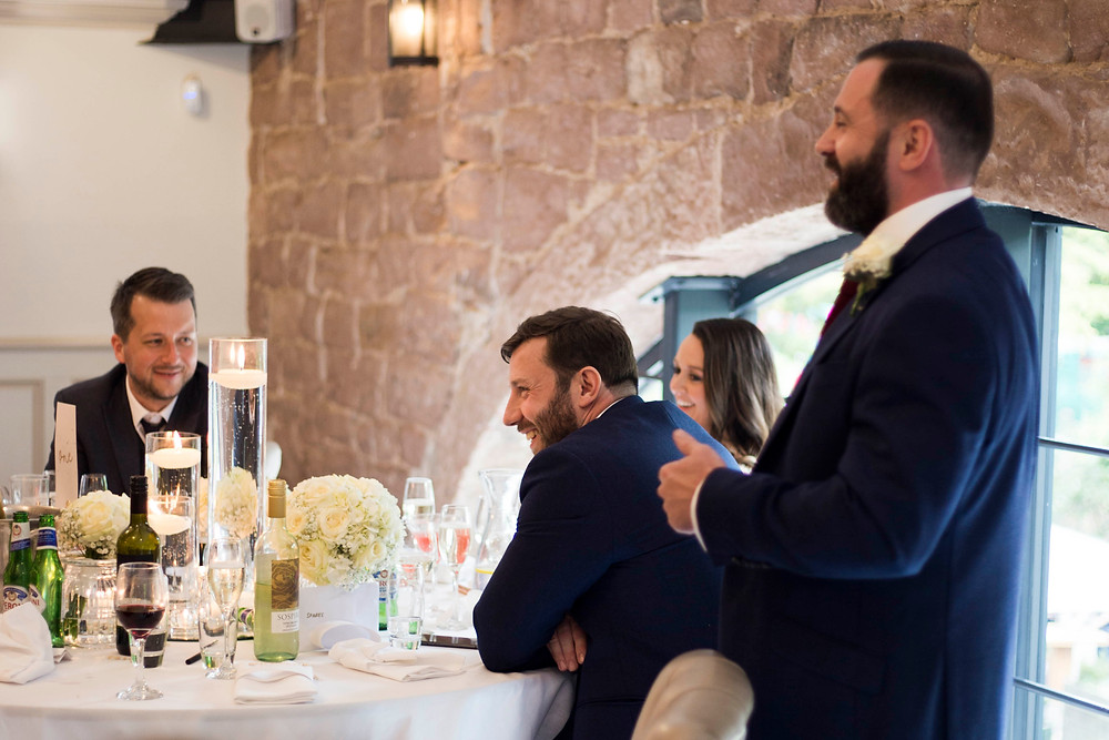 Groom laughing during best man's speech at Hayloft Allerton Manor wedding