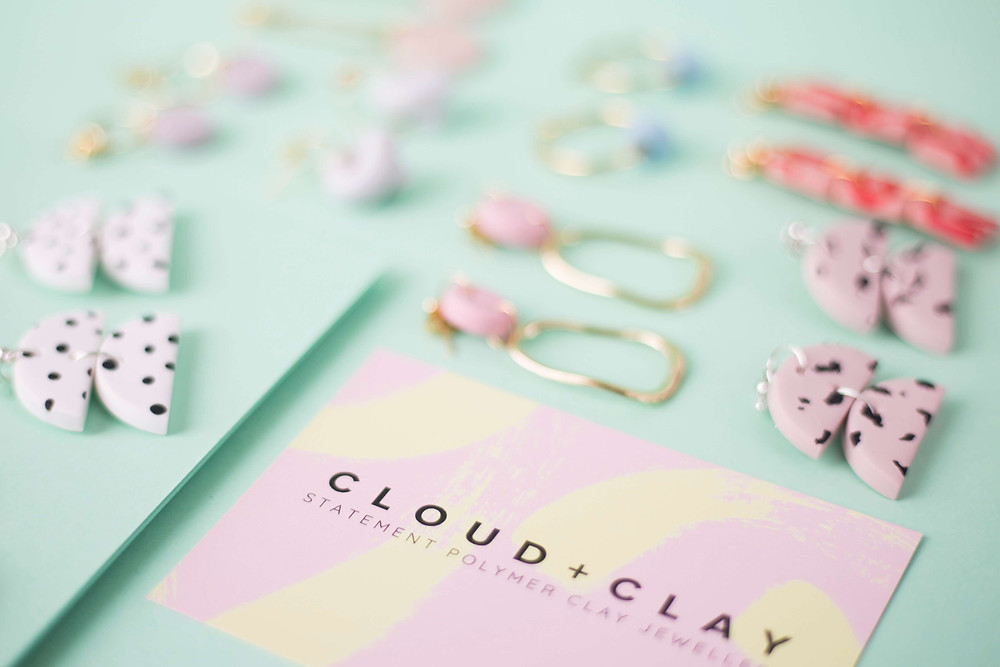 Multiple earrings and business card on pale green background. Remote product photography for Cloud + Clay