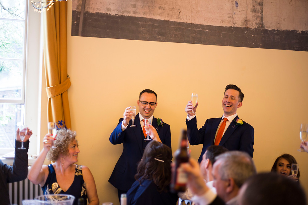grooms smiling with champagne at their bluecoat wedding