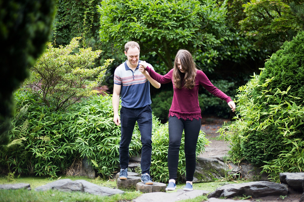 Couple walking across stepping stones in Calderstones park Liverpool pre wedding shoot